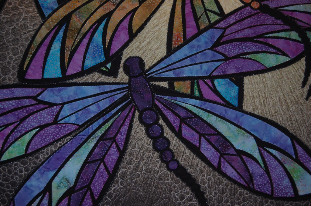 Dragonfly quilt with echo quilting and pebbles in the background