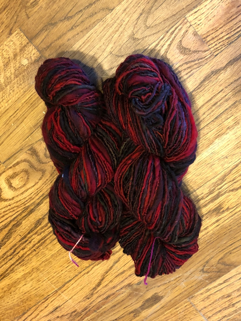 Red and black variegated Ramboillet- Columbia skein.